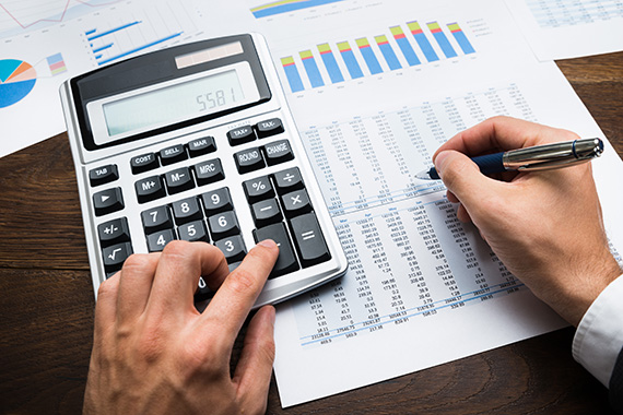 CPA uses calculator for audits, accounting bookkeeping, and financial-statements